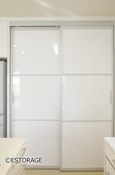 全面を白扉で見えなくした大容量のキッチンパントリー収納