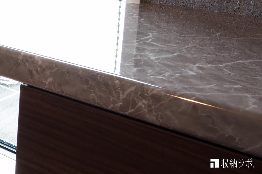 リビング収納のカウンター天板の柄は石材のイメージに。