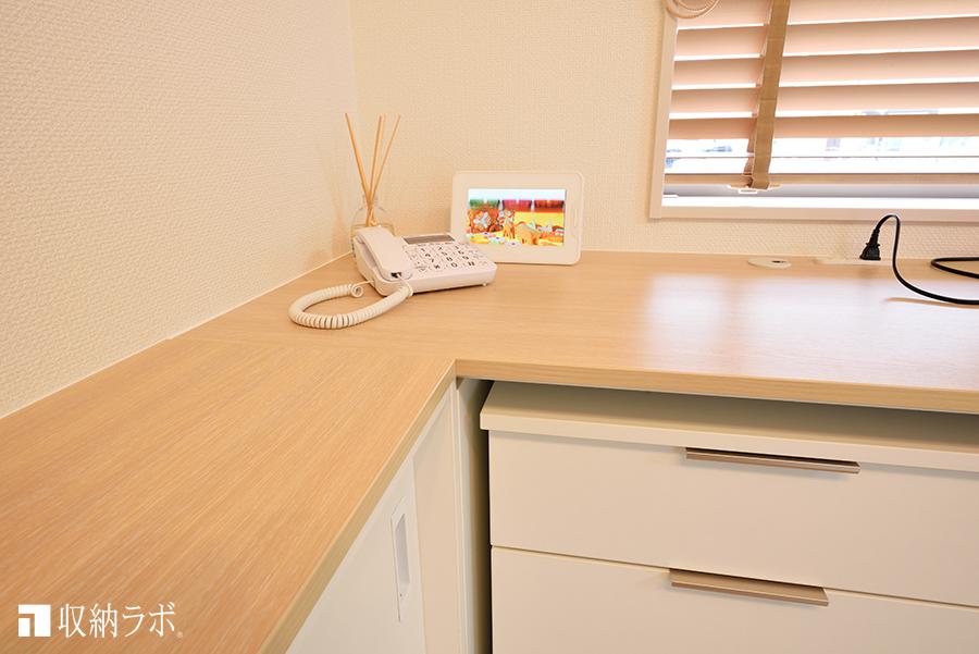 オーダー家具のL字のカウンター天板には、電話や小物を置くスペースに活用。