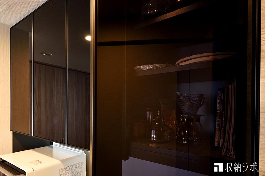吊り戸棚の扉には、見た目がお洒落で圧迫感も軽減できるスモークガラスを採用。