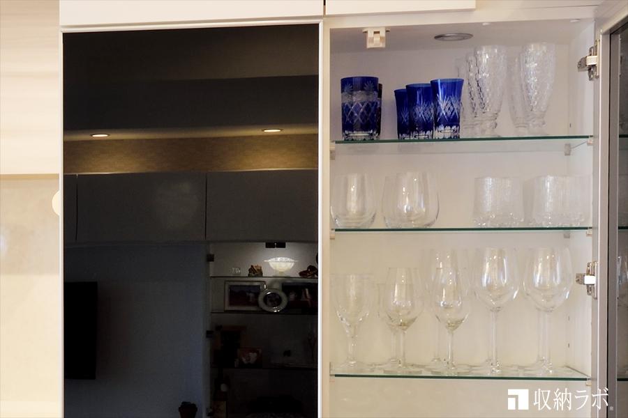 オーダーメイドの食器棚の扉には、スモークガラスを採用。照明の消灯中のイメージ。